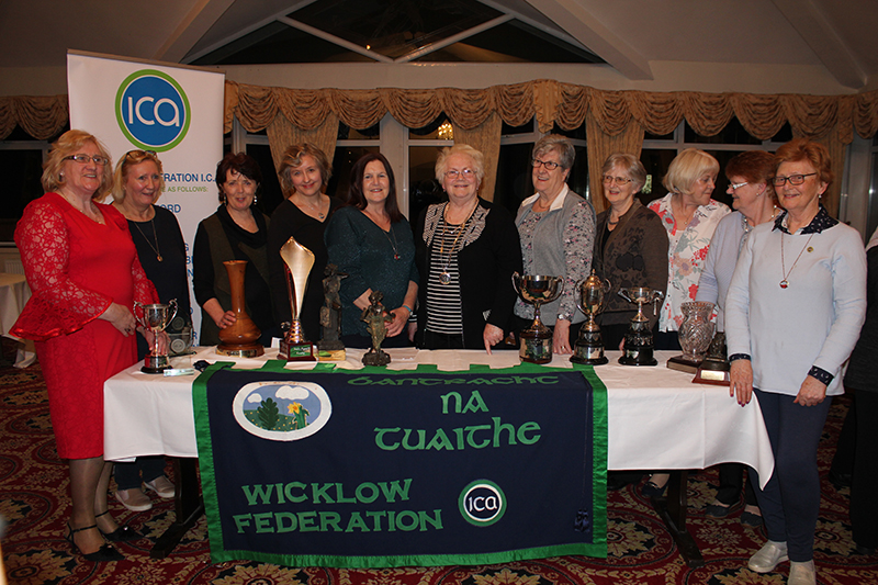 Prize Winners stand with their trophies and Cups on a table infront of them and the Wicklow Federation Banner draped over the table. Madge Kenny is in the centre of the group