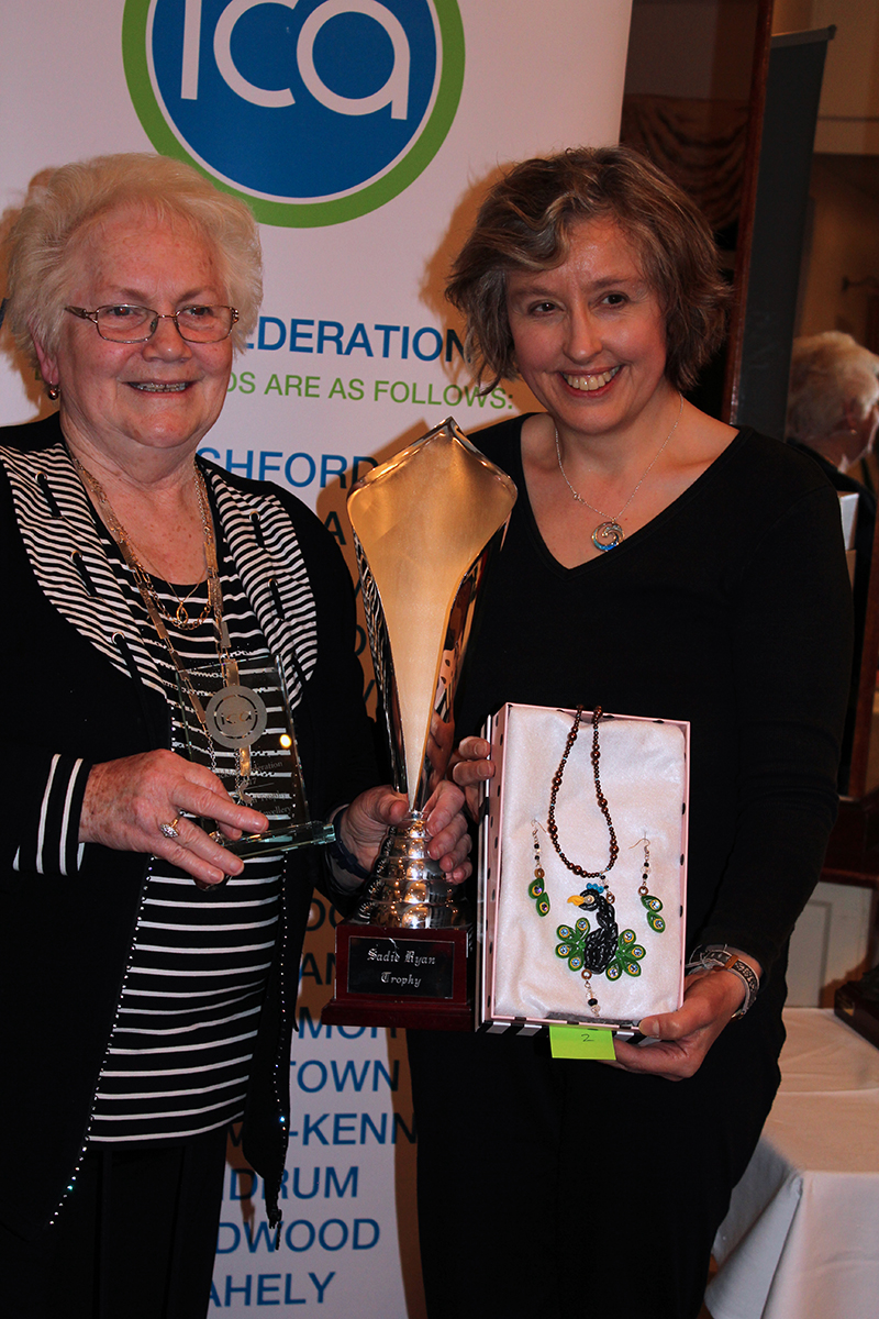 Madge Kenny, Wicklow Federation President stands with Susanna who holds a box containing her handmade peacock pendant and earrings