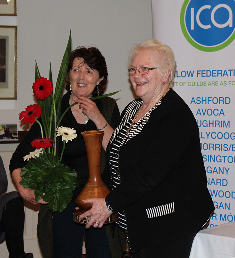 Christina holds her flower arrangement with Madge Kenny, Wicklow Federation President holding the Tinahely Show Cup, a large wooden vase.