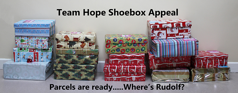 shoeboxes wrapped and stacked with text saying shoeboxes are ready where's Rudolf?