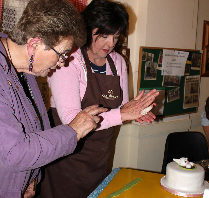 Mary Finlay watches Jennifer Doyle modelling a rabbit with white icing