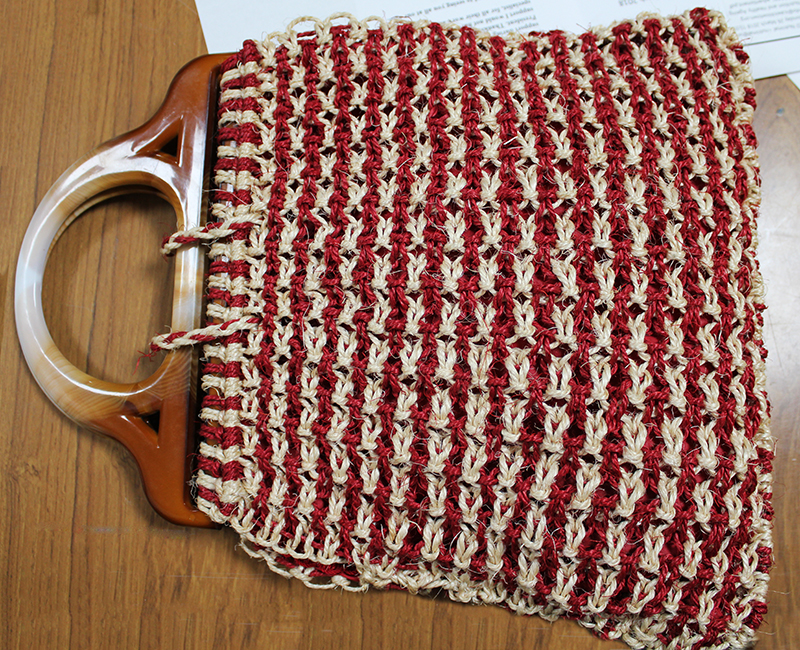 A two tone, red and cream, macrame handbag by Statia Ivers