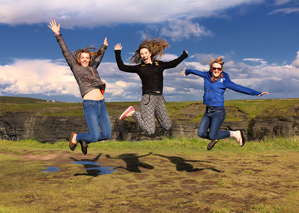 three young ladies from Northern Ireland jumping in the air at the Bridges of Ross in County Clare